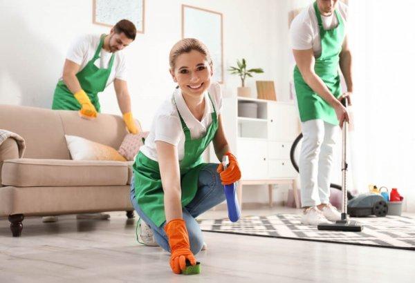 Tre personer städar ett vardagsrum