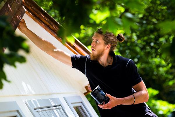 man målar trähus fasad