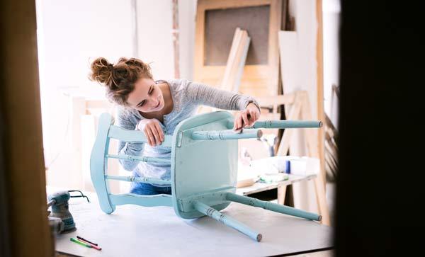 ung kvinna målar om en köksstol