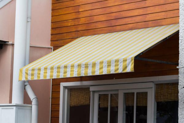 gul och vit markis på träfasad