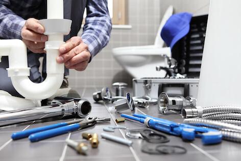 Person arbetar med rör i badrum med verktyg utspridda på golvet