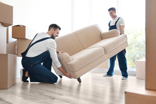 Två män lyfter en soffa omgivna av flyttkartonger