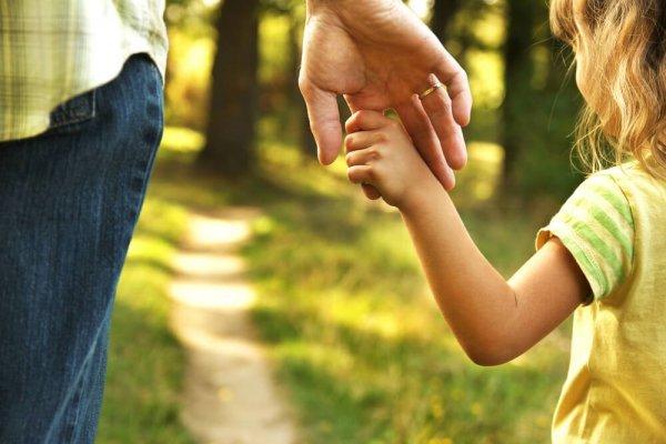 Flicka håller pappa i handen