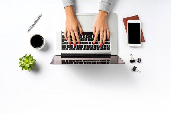 Två händer med rött nagellack knappar på laptop