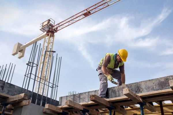 Byggarbetare på hög byggnadsställning använder hammare