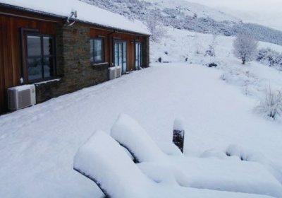Värmepumpar på utsidan av hus i snö.