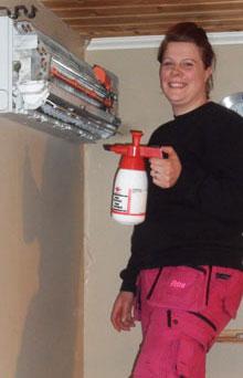 kvinnlig servicetekniker utför service på luftvärmepumps innedel