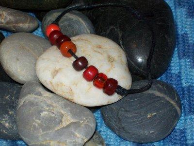 """Svart vaxad bomullstråd, med """"kongopärlor"""" av glas i röda nyanser"""