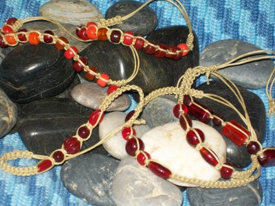 Vaxad bomull med blandade former av glaspärlor i röda nyanser