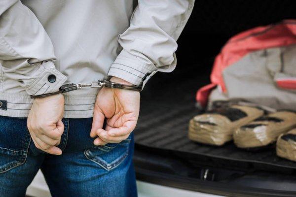 Person med händerna i handklovar bakom ryggen.