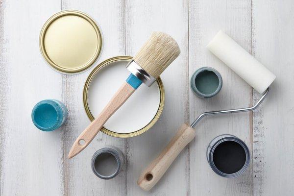 Pensel, roller och burkar med olika färger i står på ett bord