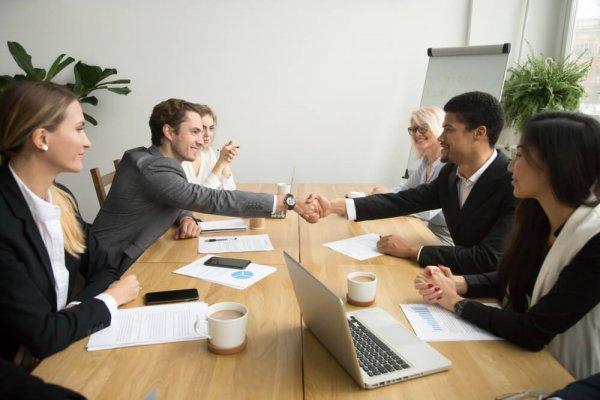 Två män skakar hand vid bord, ytterligare fyra personer sitter vid bordet
