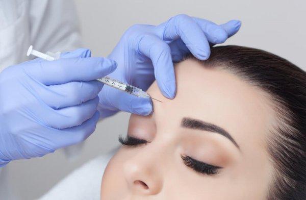 Kvinna får botoxinjektion i pannan
