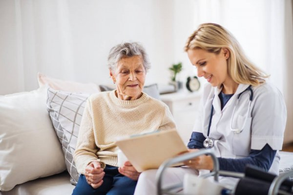 sjuksköterska läser journal för äldre dam