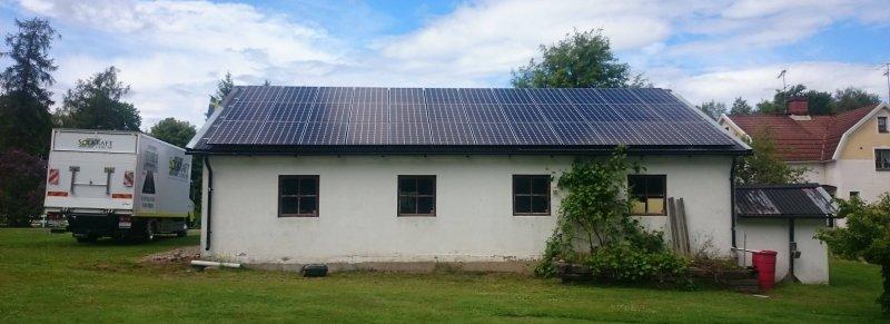 Ett tak på ett vitt hus med solceller i Örebro.