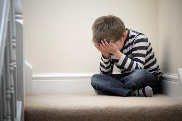Liten pojke sitter på golvet och gömmer ansiktet i händerna