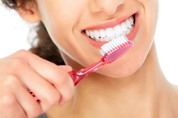 kvinna med känsliga tandhalsar som borstar tänderna