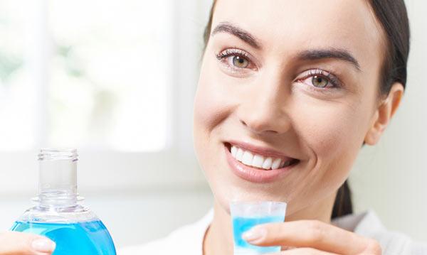 kvinna som sköljer munnen med fluor