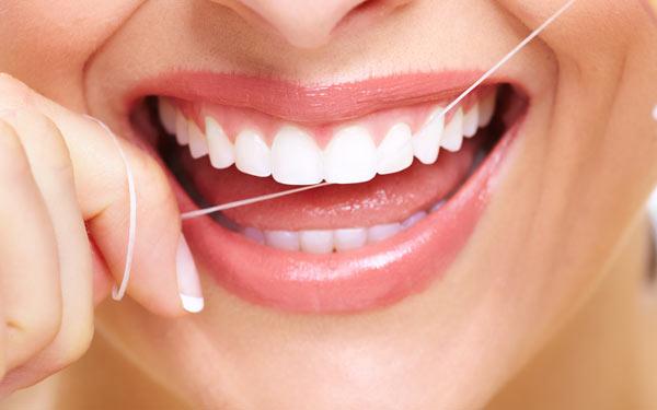 kvinna använder tandtråd