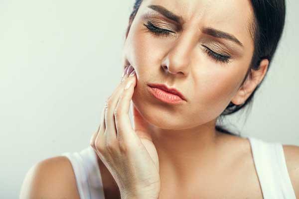 kvinna med tandvärk vid förkylning