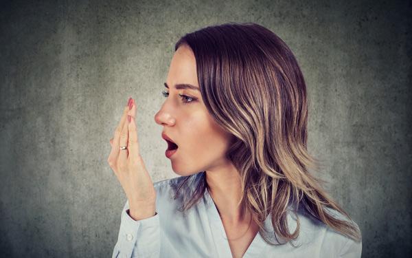 kvinna kollar om hon har dålig andedräkt