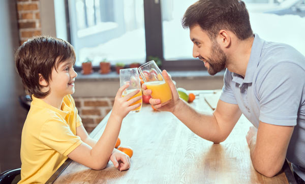 pappa och son dricker juice