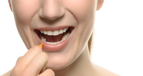 kvinna borstar mellan tänderna