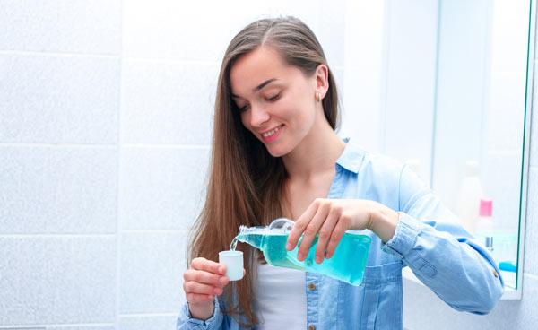 kvinna som använder munskölj