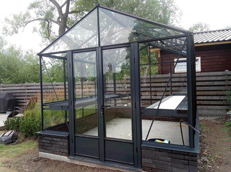 Uterum i Uppsala i form av växthus med svarta lister i en trädgård.
