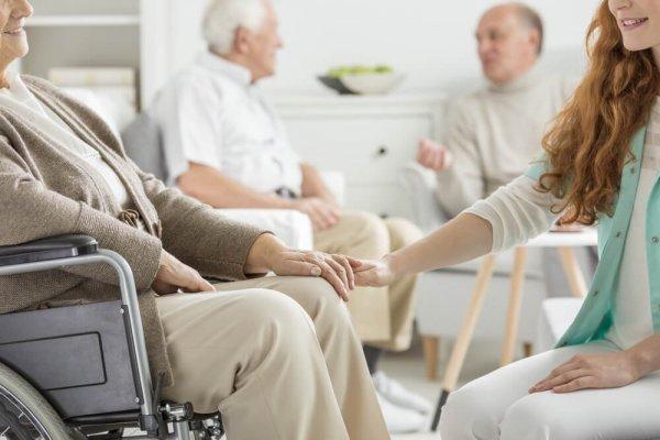 Tre äldre män och en yngre kvinna sitter och pratar på ett ålderdomshem