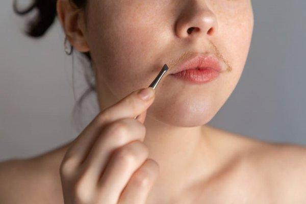 Ung kvinna tar bort hår från överläppen med pincett